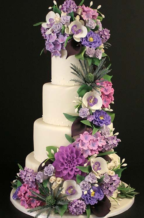 An array of purple, pink and green sugar flowers, including orchids and hydrangeas, are draped on a traditional white five-layer cake.