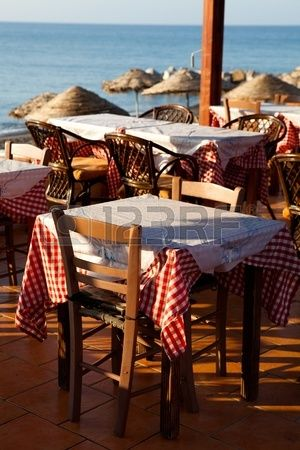Outdoor restaurant tables by the beach in Perissa Santorini Greece Stock Photo