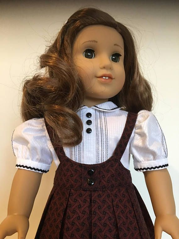 Rebecca is wearing her vintage style school jumper with an heirloom style blouse. It will fit most 18 dolls of similar body type. The jumper is made of a heritage cotton print of a deep red and black . The jumper is a low cut scoop neckline that is top stitched on around all sides.