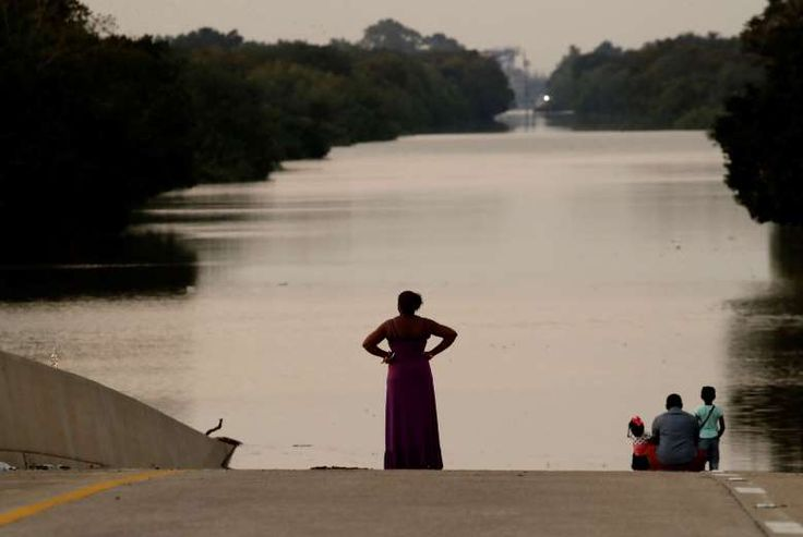 Jessica Anderson, with her husband Darrell and daughters Lauren, and Harper view floodwaters in Addicks Reservoir from a closed freeway in the aftermath of Hurricane Harvey on Friday, Sept. 1, 2017, in Houston.