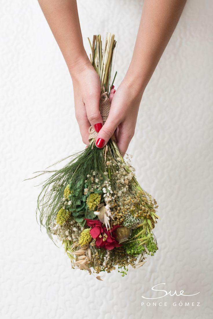 Jessica quería que su ramo fuera de estilo Silvestre a juego como la corona de flores preservadas que también le realicé para su boda. Estaba compuesta de Hortensias verdes, hojas de la falsa pimienta, avena y Rosas rojas. Todo preservado.    Fue un gran acierto para su look