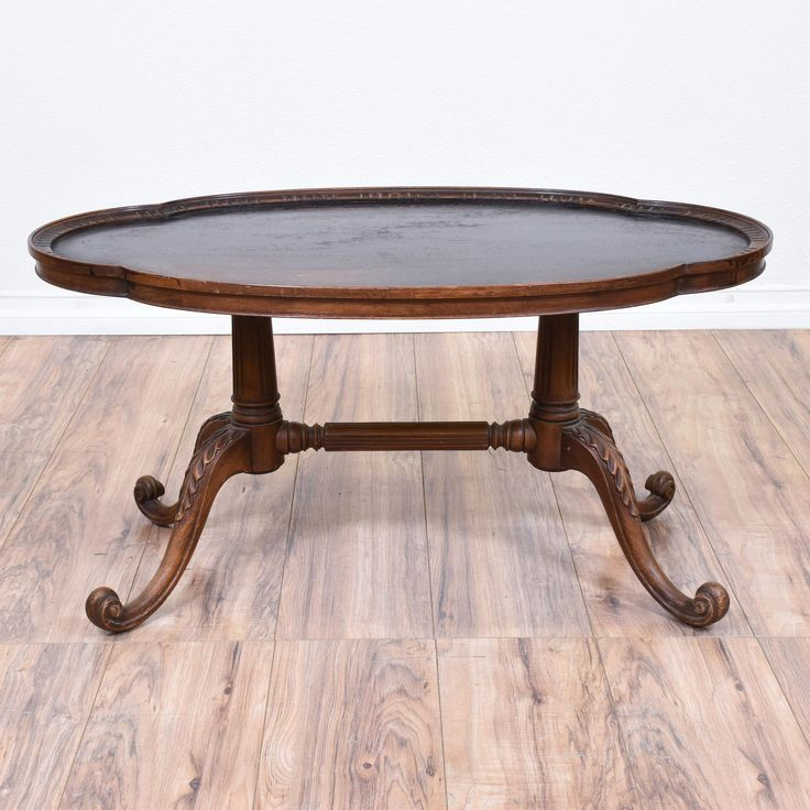 This victorian coffee table is featured in a solid wood with a rustic oak finish. This coffee table has a curved table top, a carved spindle stretcher and swirl acanthus leaf legs. Elegant table great for a small living room! #european #tables #coffeetable #sandiegovintage #vintagefurniture