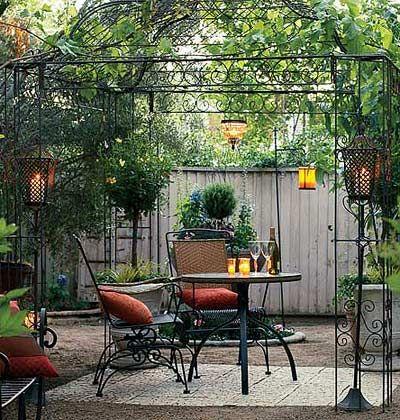 A wrought iron gazebo in a backyard.