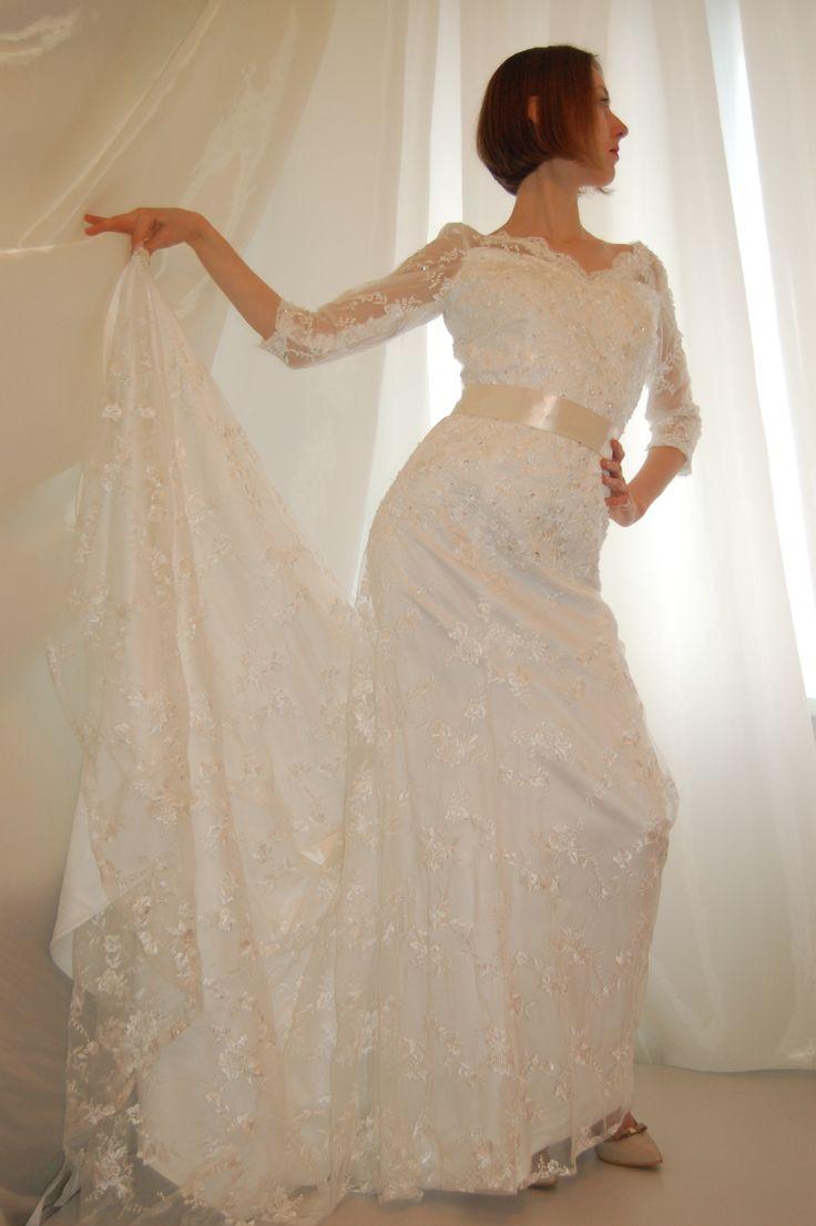 Свадебное кружевное платье силуэта рыбка, корсет с кружевным лифом с V-образным вырезом спереди и на спинке, рукав три четверти, юбка годе со шлейфом, подстегивающимся при помощи петли и жемчужной пуговицы.