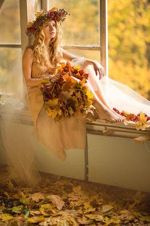 Девушка в венке из цветов и желтых листьев, сидит на подоконнике и  держит  в руке букет из осенних пожелтевших листьев