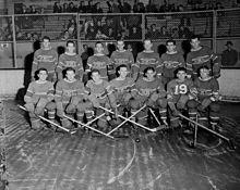 Photo noir et blanc des 14 joueurs des Canadiens de Montréal qui posent sur deux rangs sur la patinoire devant un grillage qui les sépare de...