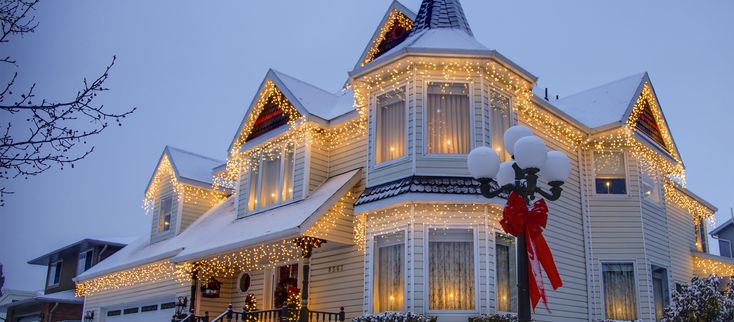 Outdoor Christmas lights ideas for decorating the roof include outlining the gutters with lights and hanging Christmas lights from eaves and roof lines.