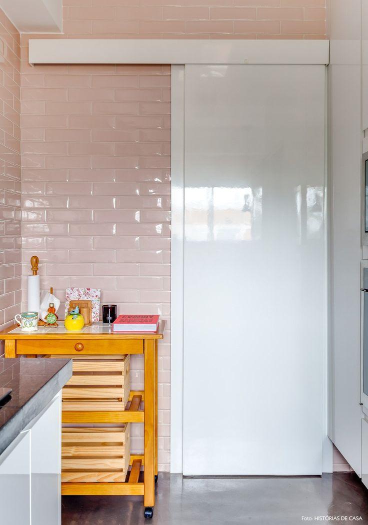 Cozinha com porta de correr de marcenaria, azulejos rosa pastel e um carrinho de apoio para louças e temperos