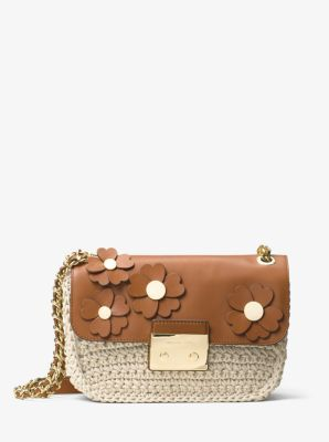 Renewed for the season with a crocheted finish and appliquéd leather florals, the Sloan shoulder bag is a luxe, ladylike essential. Glamorous gold-tone hardware accents the tactile leather exterior, while the petite shape will complement feminine ensembles.