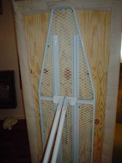 """A SERIOUS IRONING BOARD! Piece of plywood 58"""" x 24""""  was cut and screwed to a regular ironing board. Four layers of batting was attached to the top, pulled around smooth and snug and stapled on the bottom side. Stretch canvas over the whole thing and staple to underside, folding over raw edges."""