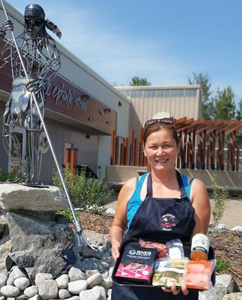 Standing in front of the kł cp'elk' stim' fish hatchery at the Penticton Indian Band, Sandy Terbasket shows off the range of preserved salmon products being marketed by the Okanagan Nation Alliance under the Okanagan Select brand. Money raised through the sale is used to support the ONA's ongoing efforts to restore the Okanagan Sockeye run. - Submitted photo