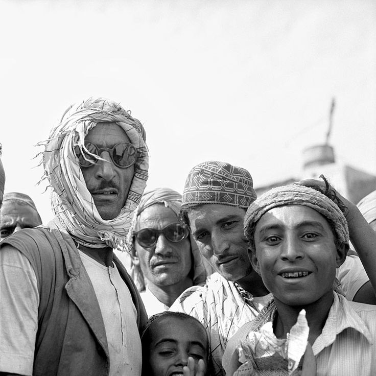 A group of six males with head coverings looking at the camera. July 10, 1959, Aden, Yemen