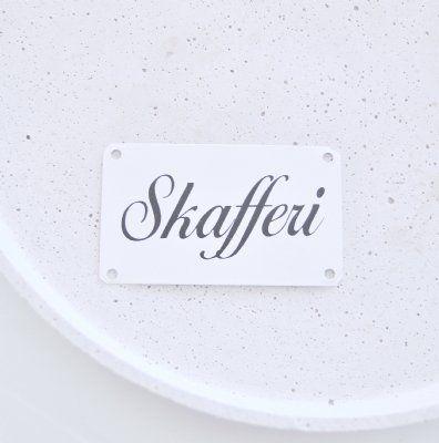 """En fin lantlig skylt i plåt med texten """"Skafferi""""."""