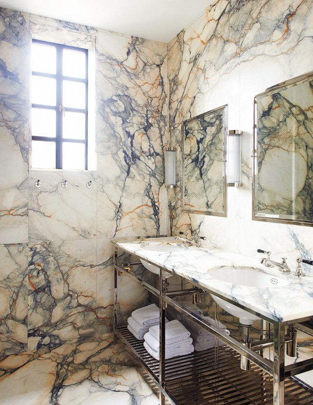 Warm all-marble bathroom with polished chrome faucets, and matching chrome mirrors