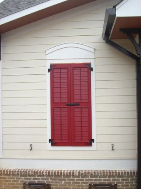 Louvered shutters with control rod closed over opening with shutter bolt home for Exterior louvered window shutters