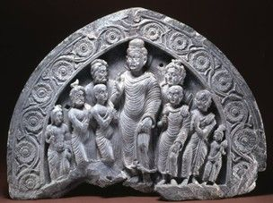 A group of figures under a pointed arcade depicting the Buddha with monks, ascetics, a prostrate figure and female: the Dipankara Jataka.
