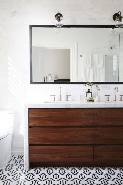 Modern bathroom with walnut vanity, hex floor, marble waterfall counter, black mirror, double sinks