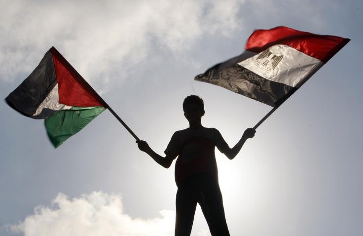 Un joven ondea la bandera palestina y egipcia para dar condolencias por 16 soldados egipcios que fueron asesinados durante un ataque contra un puesto militar en la ciudad de Gaza (Adel Hana/AP)