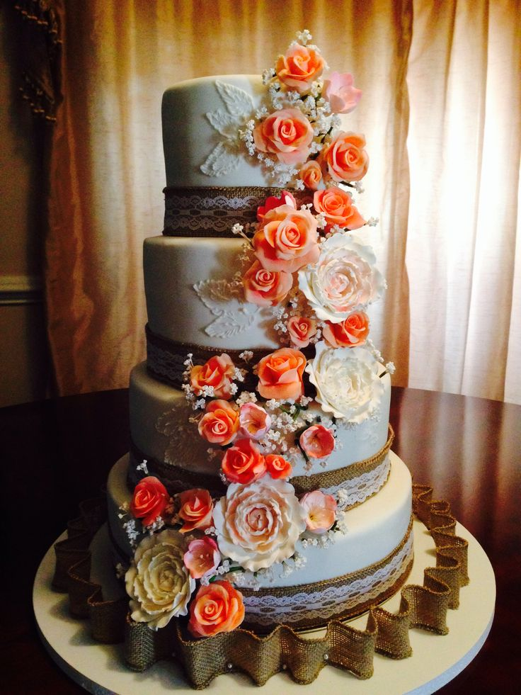 Wedding cake with burlap and lace elements. Handmade coral sugar roses. Made by Sonia Ackley