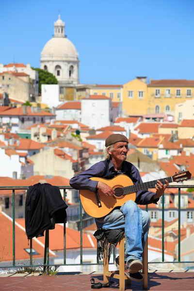 Street musician is playing on his flamenco guitar in Lisbon, Portugal with the National Pantheon in the background.