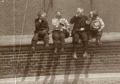 Hitte, hittegolven, droge moesson. Vier jongens vegen het zweet van hun voorhoofd met een zakdoek af,  tijdens de hittegolf in Amsterdam, Nederland 1910.