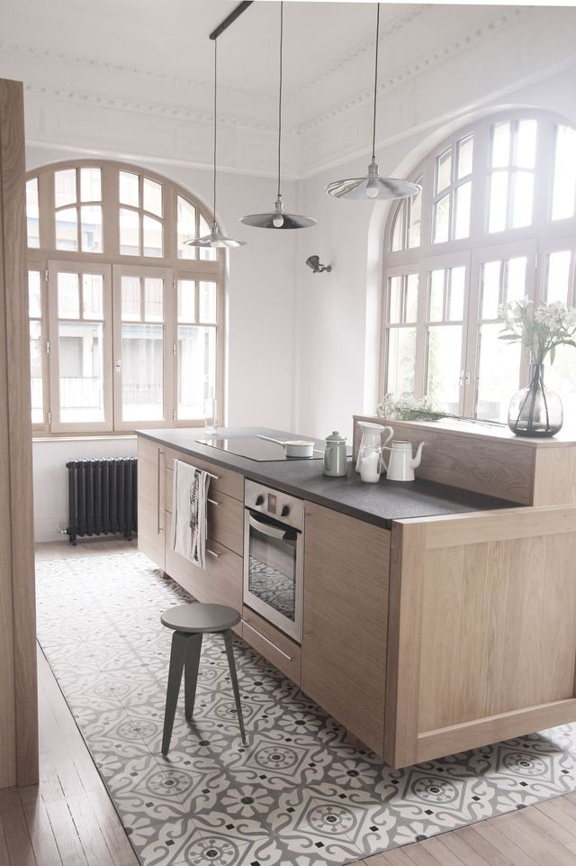 Un îlot de cuisine en bois clair mis en valeur par des carreaux de ciment