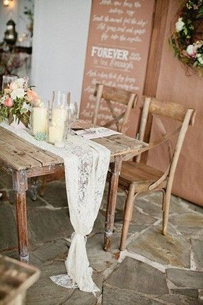 Lace table runner on a rustic wood wedding table.