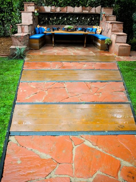 The wide stone-and-metal pathway and tiered outer walls set this outdoor dining booth up to be a focal point. Blue throw pillows and seat cushions provide notice-me contrast to the Southwestern-style stone features. Design by Jamie Durie