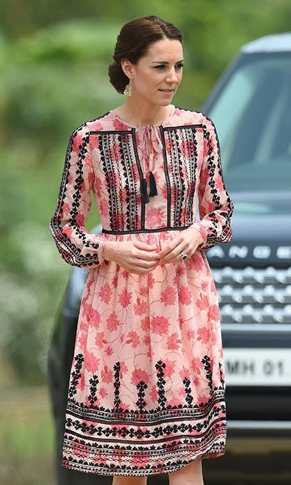 Showing us all how to do high street, Kate modelled a stunning pink Topshop dress with intricate black embroidering, and added a touch of sparkle to the look with her bargain $14 earrings from Accessorize.  Photo: © Getty Images