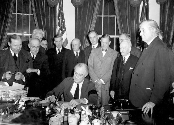 President Roosevelt signs the declaration of war following the Japanese bombing of Pearl Harbor, at the White House in Washington, District of Columbia, on December 8, 1941.