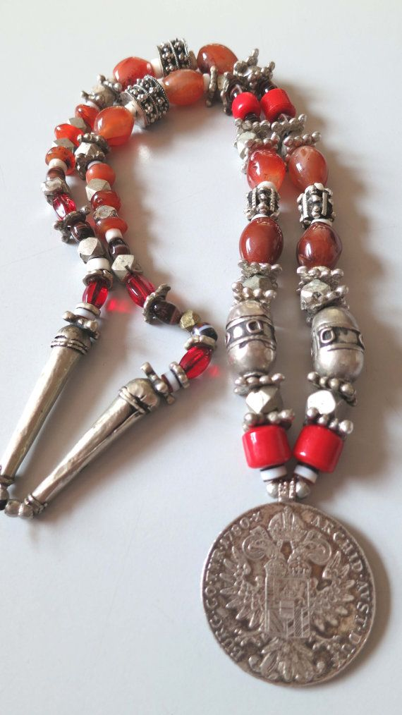 Original vintage Najran Saudi Arabia Arab Yemen Bedouin necklace with beautiful old silver beads, Maria Theresia Taler, cornelian beads and red glass beads. The large center pendant is made from a Maria Theresia Taler. The necklace has lots of old silver Yemeni beads, cornelian and red glass beads and 2 tube beads of 5 cm (2) in the neck part. length of the necklace all around is 82 cm (32), weight is 235 grams. The necklace has no opening clasp but will go over your head!  If you have any…