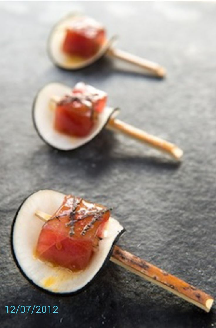 Seared ahi tuna cube in spices, pierced with a toothpick, placed on a thin slice of cucumber