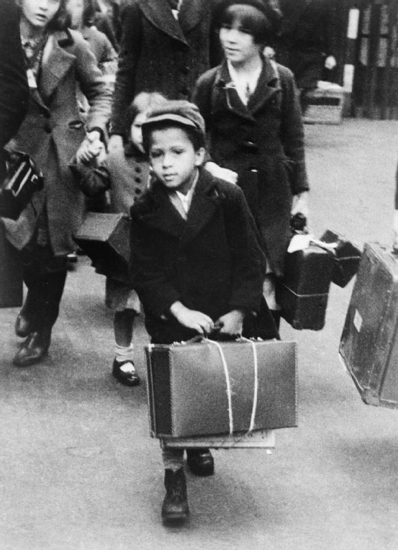 A small black boy carrying his luggage as he left London for the country with a party of other evacuees on 5 July 1940.