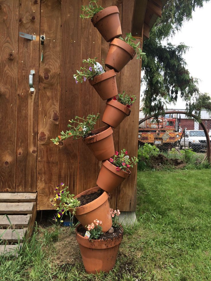 Saw a smaller scale of this on Pinterest with painted blue pots...... Naturally when I attempted it I could not pound the rebar into the ground any further so I had to stack higher and used a much larger pot for the bottom..... Let's see how she hold up in the wind!!