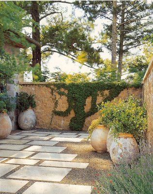 Ron Lutsko Jr. wraps honey-hued stone walls around the courtyard and uses large limestone pavers surrounded by gravel instead of grass