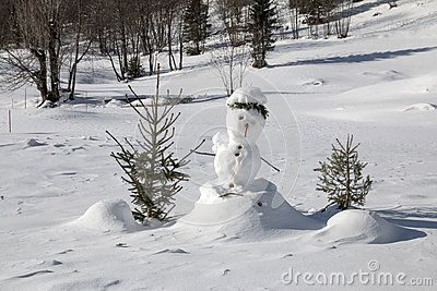 Funny snowman around two small trees