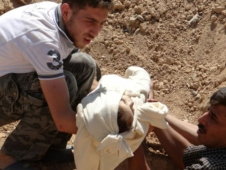 Сирийцы кладут тело ребенка в братскую могилу на окраине Дамаска.