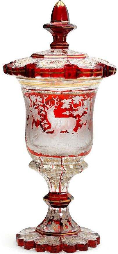 A Bohemian part ruby-stained goblet and cover, circa 1840-50 Of campana shape, the front ruby-stained panel engraved with a stag and doe, the broad-fluted crystal glass ground with floral sprays and scrollwork in white enamel heightened in gold, three viewing lenses within ruby panels, the heavy scalloped foot and the petal-cut cover also enamelled with floral scrollwork within panels delineated in red, 22.7cm high (2)