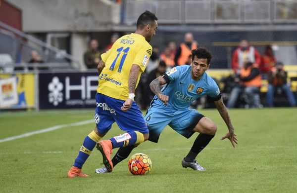 Barcelona's Brazilian defender Dani Alves (R) vies with Las Palmas' midfielder Momo during the Spanish league football match UD Las Palmas vs FC Barcelona at the Gran Canaria stadium in Las Palmas de Gran Canaria on February 20, 2016.