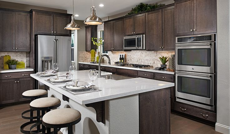 Warm wood tones and stainless-steel appliances combine to create a modern, inviting space in Mountain House, CA | Charlene plan by Richmond American