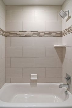 We love oversized subway tiles in this bathroom! The addition of glass accent tiles gives the space a custom look without being over the top. This is perfect for your secondary bathrooms. We also love the square showerhead from the  Dryden collection.