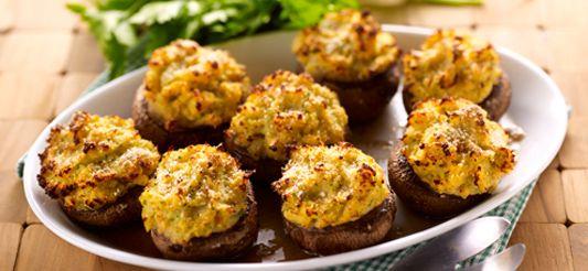 Verwarm 2 eetlepels olie in een grote braadpan en bak er de gesnipperde ui in aan. Dek af en laat 10 min. stoven op zacht vuur.     Pel ondertussen de ontdooide scampi's en snij ze in stukken (je hebt er 100 g netto van nodig). Breek de steeltjes uit de champignons en hol de hoedjes een beetje uit met behulp van een aardappelboor. Zet opzij.     Verwarm de oven voor op th. 6 – 180°C.     Doe de in stukken gesneden kabeljauw bij de ui en laat 2 min. op zacht vu...