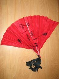 waaier maken door een a4 blad te versieren met zwarte stift en hier met rode ecoline overheen te gaan. Dan om en om vouwen. Onderaan vastnieten en een klein zwart slingertje eraan.