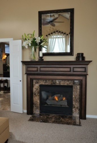 Classy traditional fireplace with mirror. TVs above fireplaces... gross! I would replace the stuff on this mantle with 2 candles and 2 smaller flower bouquets on either side.