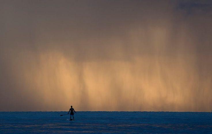 """Un ragazzo pratica lo """"stand up paddle"""", una variante del surf in cui si sta in piedi su una tavola e ci si sposta utilizzando una pagaia, prima di un temporale a Bal Harbour, Florida, Stati Uniti (AP Photo/Wilfredo Lee)"""