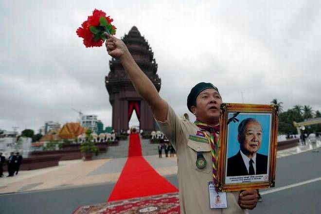A Cambodian scout holds a picture of late king Norodom Sihanouk in Phnom Penh on November 9, 2017 as the South-East Asian country celebr...
