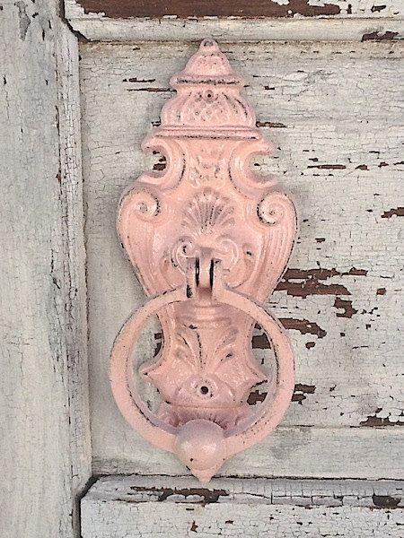 Weathered pink door knocker.