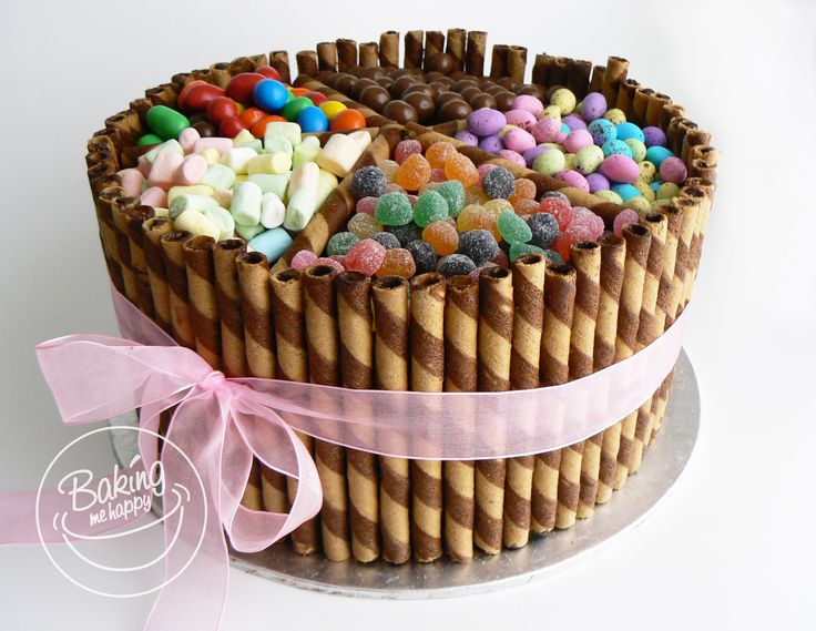 Three layer Dark, moist chocolate cake with chocolate ganache filling and Frosting. Surrounded with chocolate wafer straws and topped with candy. #Candycake #Waferstickcake #BakingMeHappy