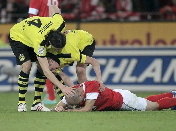 Die Dortmunder Neven Subotic (l) und Sven Bender (M) zeigen Fairness und kümmern sich zuerst um den verletzten Mainzer Elkin Soto. (Foto: Fredrik von Erichsen/dpa)