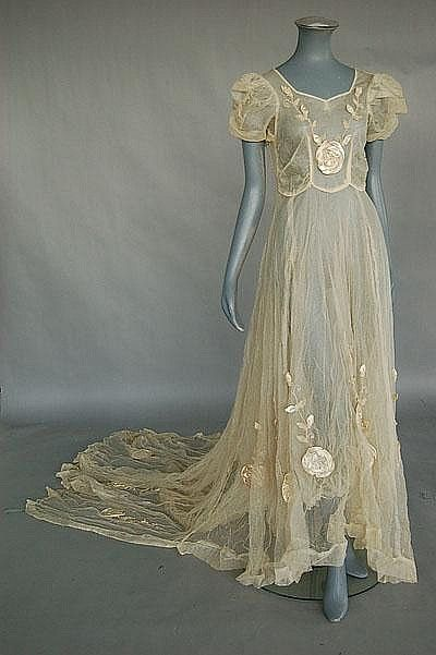 Description: An ivory tulle bridal gown and headress circa 1935, the bodice and long, trained skirt adorned with large satin roses and chenille embroidery, one optional detached sleeve, bust... Front